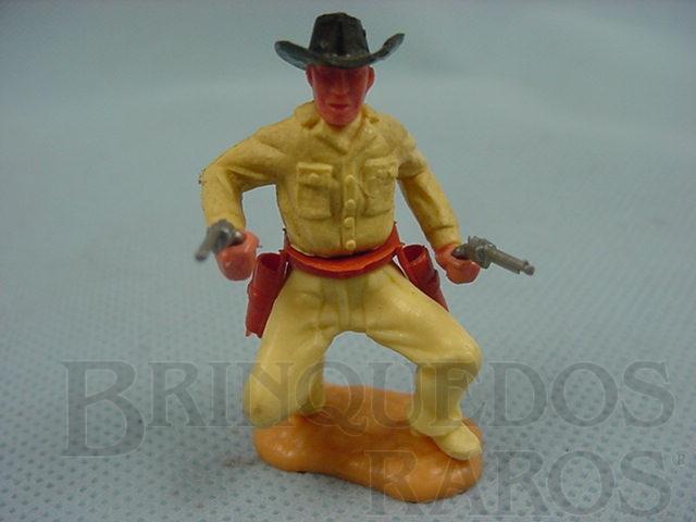 Brinquedo antigo Cowboy de pé com dois revolveres