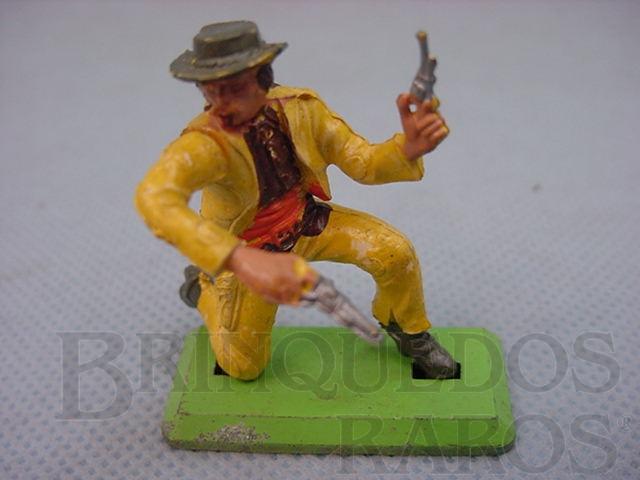 Brinquedo antigo Cowboy ajoelhado com dois revolveres Série Deetail Década de 1970